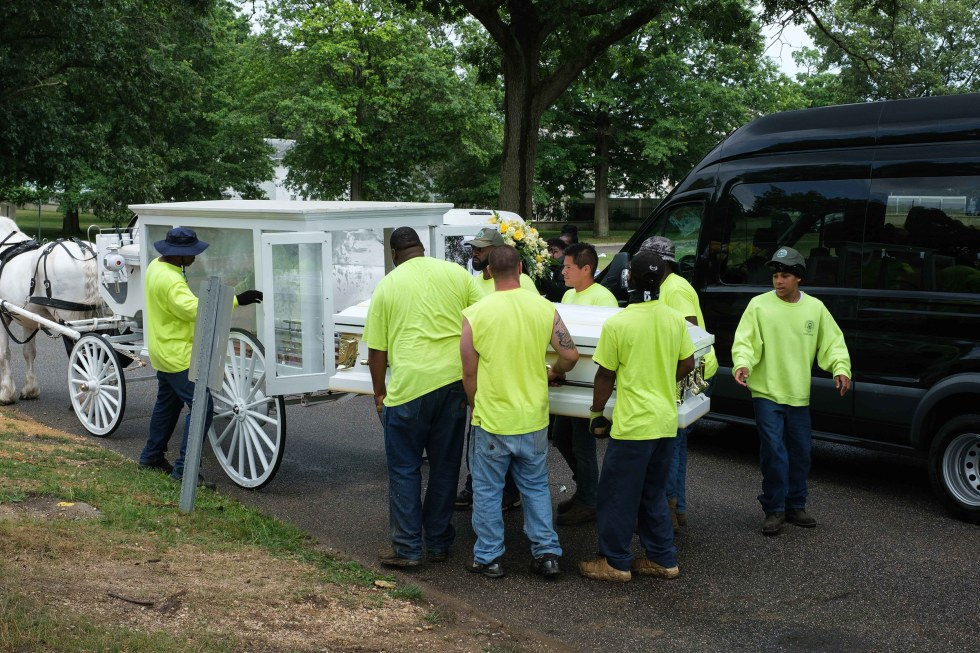 Cemetery workers carry Jamel Floyd's coffin to the burial site at Greenfield Cemetery in Hempstead, N.Y., on June 30.