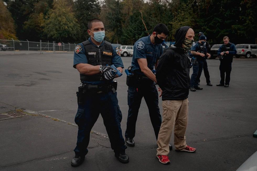 Police recruits Francisco Araiza, left, and Omar Figueroa, go through a high risk vehicle stop exercise.
