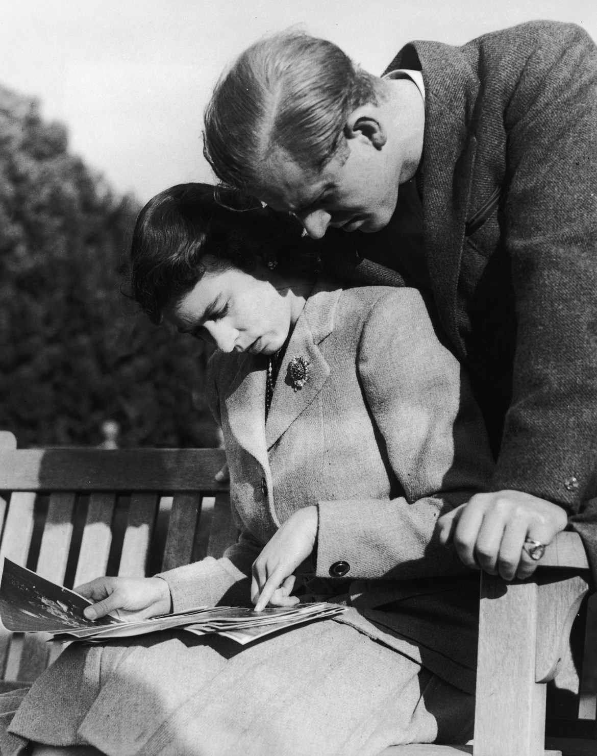 Princess Elizabeth and Philip Mountbatten look at their wedding photographs while on honeymoon in Romsey, Hampshire, Nov. 1947.