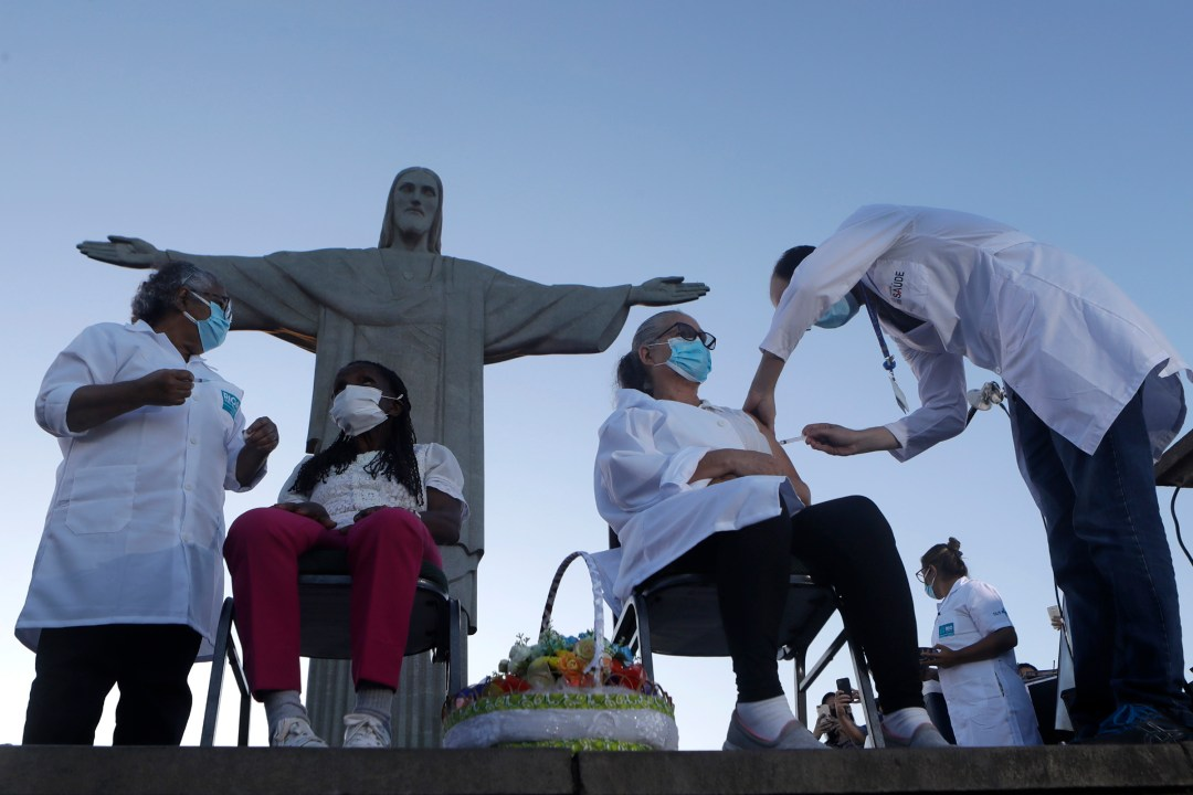 Terezinha da Conceicao, 80, left, and Dulcinea da Silva Lopes, 59, become the first women to receive the COVID-19 vaccine produced by China's Sinovac Biotech Ltd in front of the Christ the Redeemer statue in Rio de Janeiro on Jan. 18, 2021.