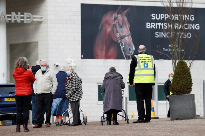 People arrive at Epsom Downs Racecourse as it opens as a COVID-19 vaccination center in Epsom, England, on Jan. 11, 2021.