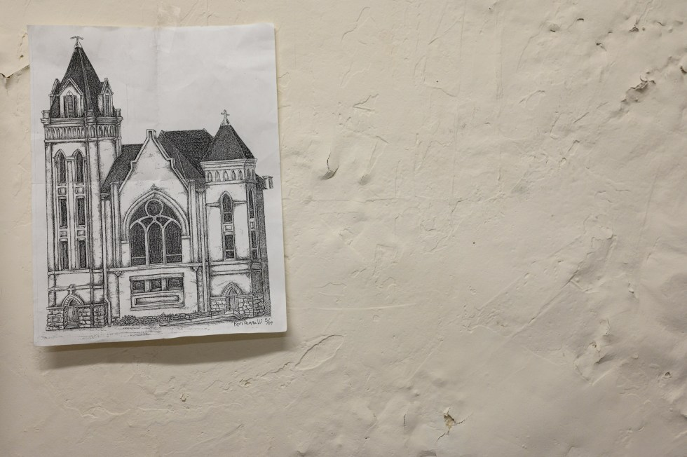"A drawing by Ron hangs in the makeshift office of ""Street Mom"" Susan Brossman in the basement of Youth Social Services, March 16, 2020. The drawing was given to Susan by Ron, who is unhoused in Wheeling, WV. Ron drew this image of a church that he could see from his window at a crisis unit for detox. Ron has been in the crisis unit over twenty times."