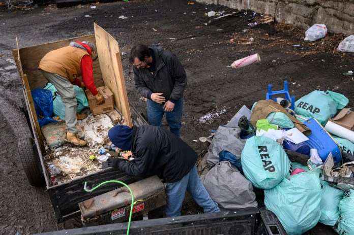 Paula Riethmiller and volunteers Gene and Michael dispose of trash found in encampments at the city dump in Wheeling on Dec. 21. Riethmiller helps lead Trash Talkers, an operation formed during the pandemic by the unhoused to solve trash accumulation in their tent encampments. Unhoused volunteers can earn gift cards and items such as phones through their volunteerism with the program.