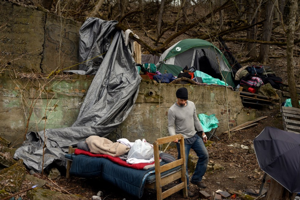 "A man who goes by the name ""Seven"" builds up his tent encampment in Wheeling, WV on March 16, 2021. When the Winter Freeze shelter closed for the year, the unhoused population had to prepare to live outside for the remainder of the year."