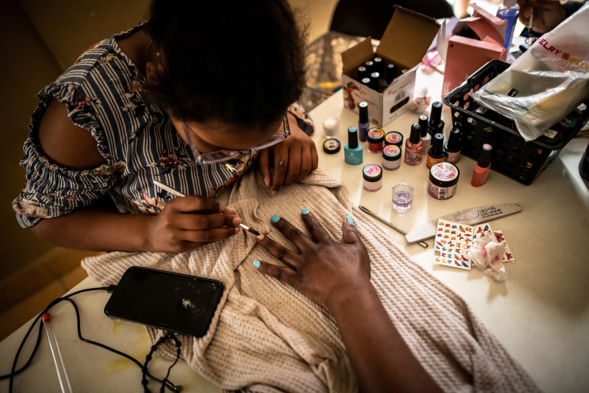 Migrants give each other gel manicures. Manicuring is one of the most accessible jobs migrant women can attain to earn an income in Ciudad Juárez. The shelter funds some women to get professional training, and then they share what they've learned by training other women at the shelter.