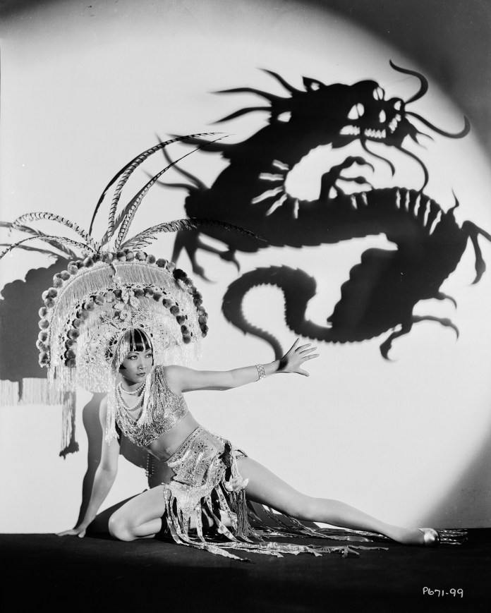 Chinese-American film star Anna May Wong wearing an exotic costume and headdress, circa 1931. Above her is a projected shadow of a dragon.