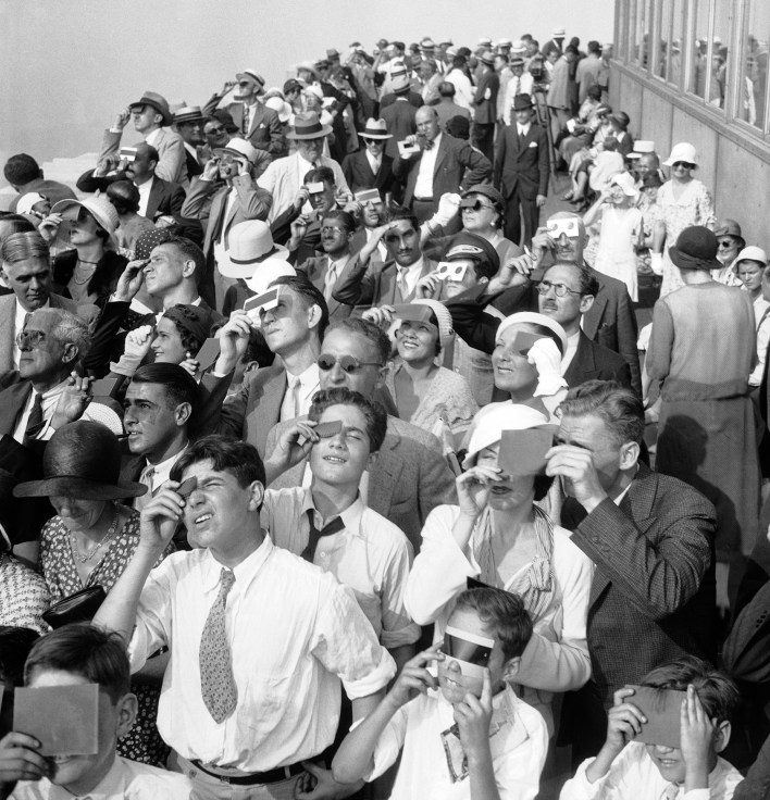 Eclipse watchers squint through protective film as they view a partial eclipse of the sun from the top deck of the Empire State Building on Aug. 31, 1932.