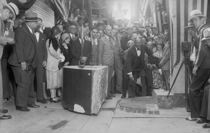 As possessor of a gold membership card in the bricklayers' union, Alfred Smith performed a thorough job when he laid the cornerstone for the Empire State Building on Fifth avenue and 34th street, New York City, before a crowd of onlookers on Sept. 9, 1930.