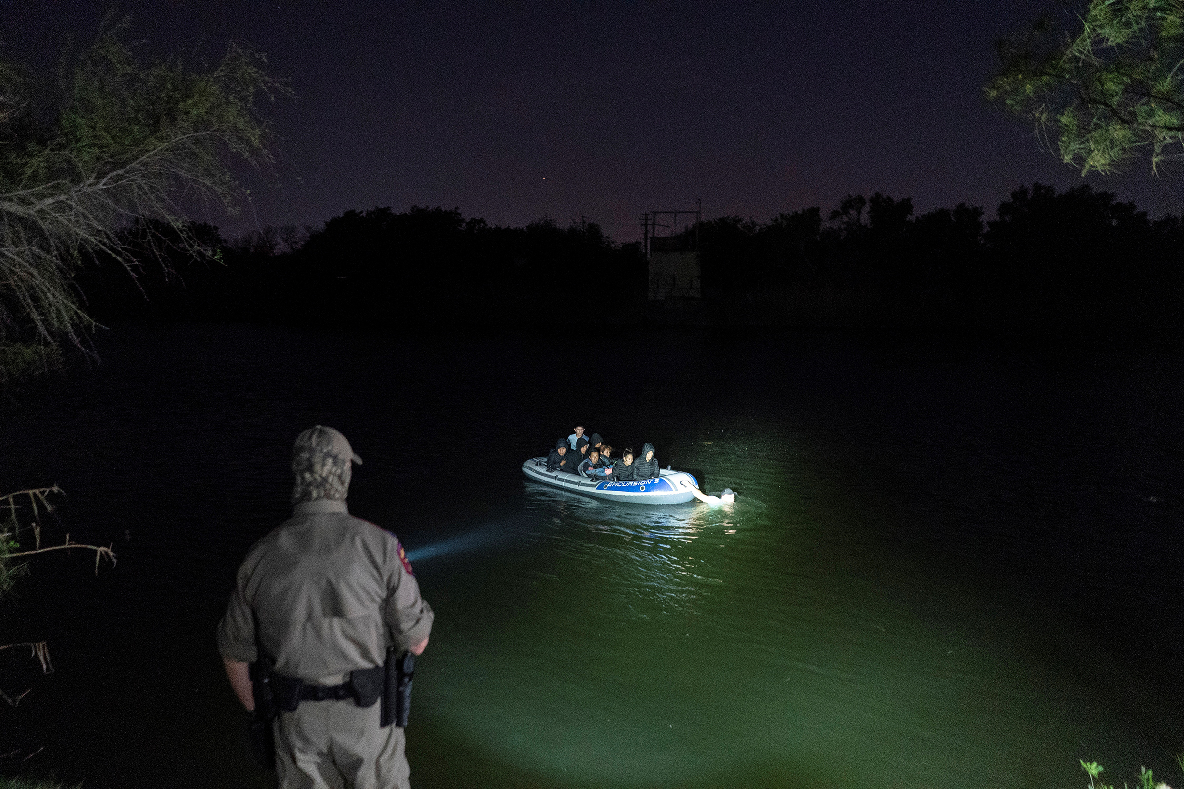 Asylum-seeking migrants' families cross the Rio Grande from Mexico as a Texas State Trooper officer points a flashlight at the inflatable raft in Roma, Texas, on April 8, 2021. The raft later turned back to the Mexican side and did not land on the U.S. side of the river.