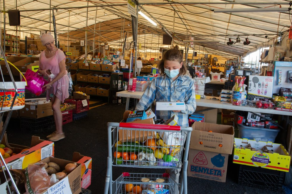 Paula and Max shop at a seasonal market for dented cans and near-expired foods at the Quartzsite Grocery and Drug Store on Feb. 8. The market caters to the mobile living community, which swells during the winter time with people seeking the warm weather.