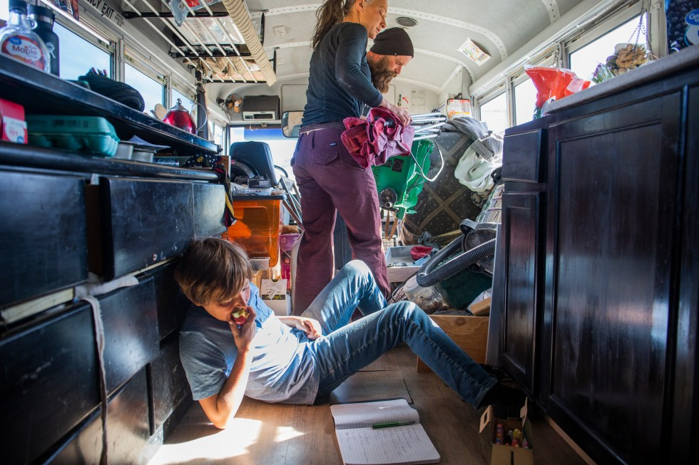 Max works on chemistry schoolwork on the floor of the bus, while Paula lends her table saw to a neighbor to work on his own bus on Feb. 23.