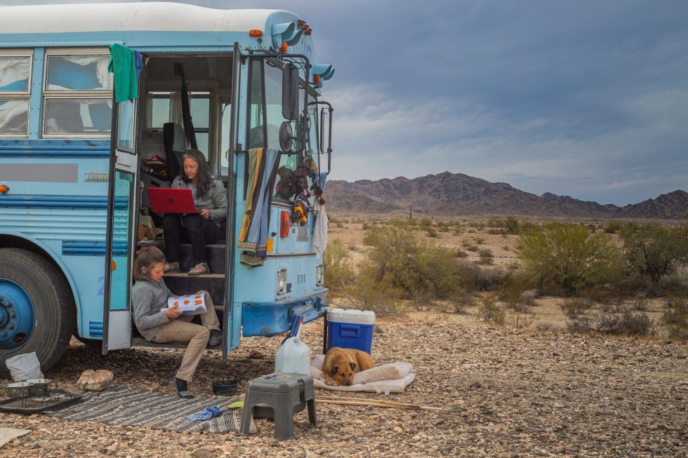 """Paula searches for jobs on her laptop while Max makes an origami card for a family member, while parked at a campsite near Quartzsite, Az., on Feb. 9. Paula says she moved into the skoolie in part in the face of economic instability caused by the pandemic. """"I'm a single mom,"""" she tells TIME. """"There's not going to be anything to catch me."""""""