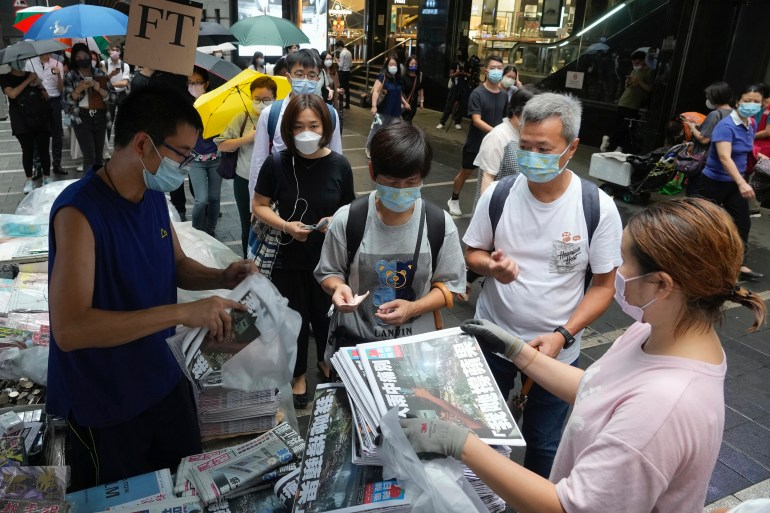People queue up for last issue of Apple Daily at a newspaper booth at a downtown street in Hong Kong, Thursday, June 24, 2021. Hong Kong's sole remaining pro-democracy newspaper has published its last edition. Apple Daily was forced to shut down Thursday after five editors and executives were arrested and millions of dollars in its assets were frozen as part of China's increasing crackdown on dissent in the semi-autonomous city.