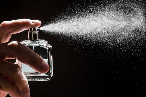 spraying perfume on dark background, closeup - Image