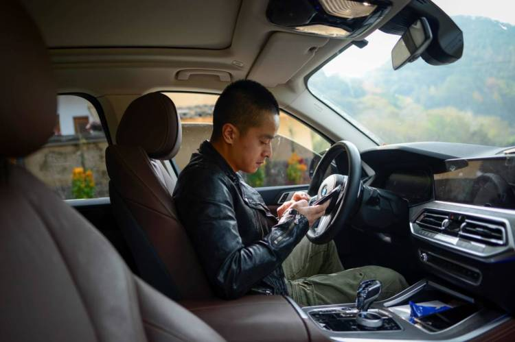 Ma looking at his mobile phone in his car before driving to his apiary in Songyang county.