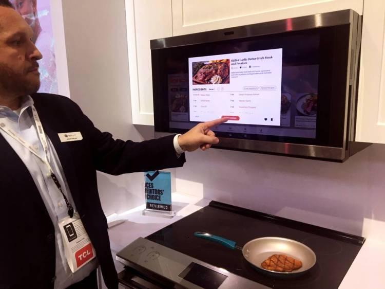 A GE Appliances employee showing a smart hub which uses AI to help consumers with meal planning and preparation, at the 2020 CES in Las Vegas. — AFP