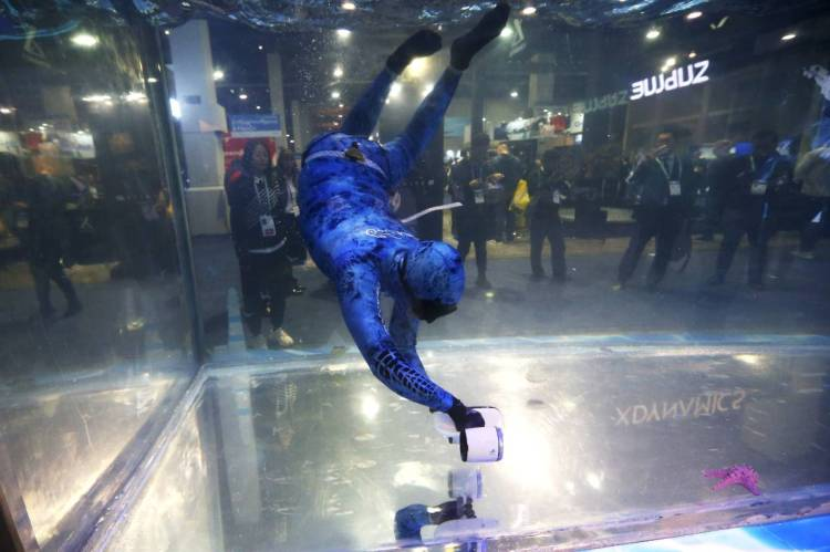A diver moving around with the Sublue WhiteShark Mix outfitted with dual propellers for power and balance at their water tank booth during the CES tech show in Las Vegas. — AP