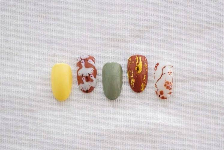 Birds and cherry blossoms lend a Chinese New Year festive feel to this nail art that is complemented with auspicious gold streaks. — Jac & Ivy Nail Spa