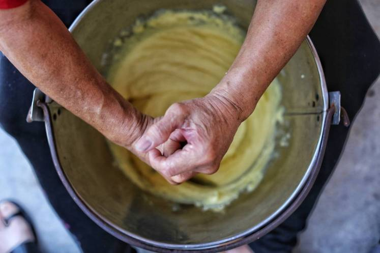 The kuih bahulu batter is mixed by hand, using a wooden spurtle.