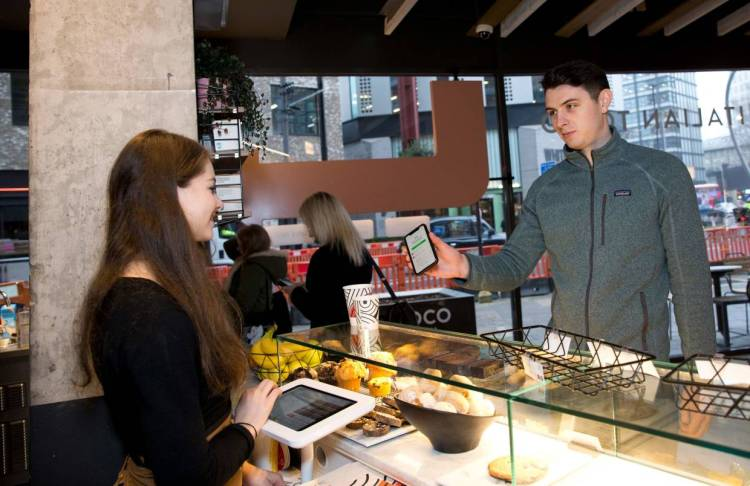 A Karma app user collecting his food, ordered through the food-sharing app, from a Coco Di Mama food outlet in London. Britain's cafes and restaurants are embracing apps that generate some revenue from rescued food that would otherwise be destined for landfill.