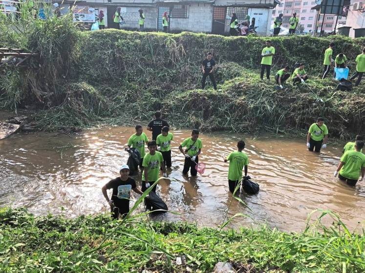 Young students helping to clean up Sungai Batu. Photo: Rolpop