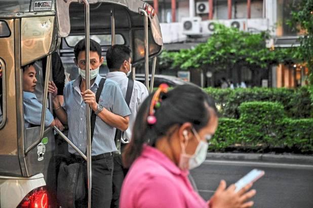 由于担心Covid-19冠状病毒的爆发,人们在曼谷晚上通勤时在公共交通工具上戴防护口罩。 -法新社