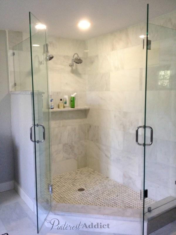 Double shower heads - marble shower shelf - basket weave tiles