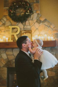Groom and Baby Near Candle-Lit Fireplace at Tundra Lodge