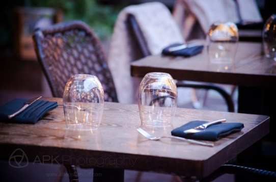On a cozy restaurant patio, wine glasses and blankets await dinner guests