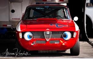 Racecar humor, in the paddock, a 1966 Alfa Romeo Giulia GTV sports eyes over headlights at Laguna Seca during the Reunion events of Monterey Car Week
