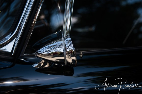 Dark tones and chrome reflections of a classic car, seen at the Carmel-by-the-Sea Concours on the Avenue event during Monterey Car Week