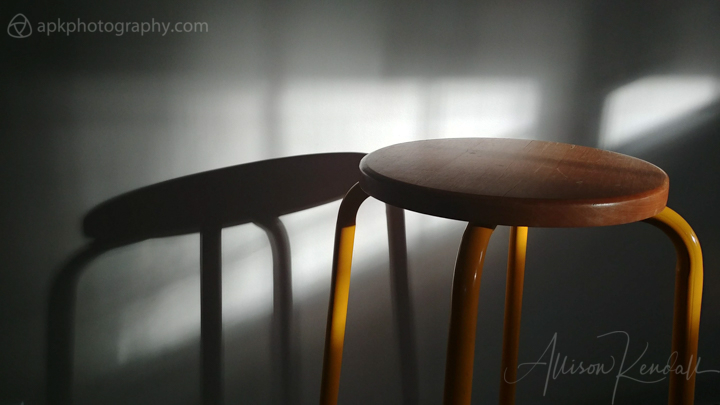 Yellow stool shadowplay, winter light across a wall