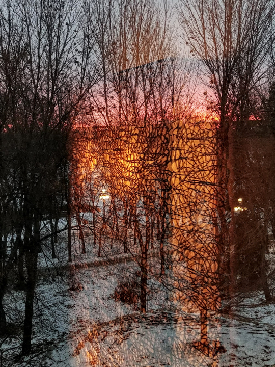 Abstract reflection of lights in a window, with a dark sunset in the distance