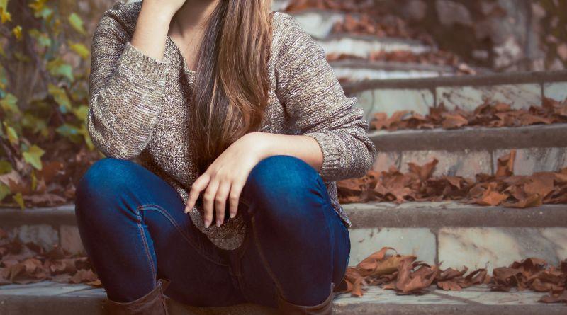 Junge Frau sitzt auf Stufen im Freien. Herbst. Blasenentzündung