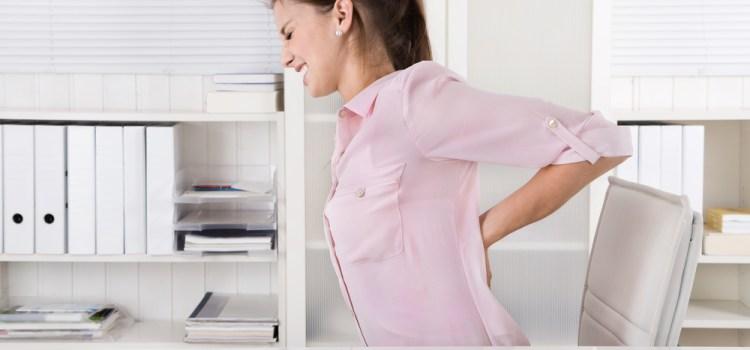 Frau in Büro hat Rückenschmerzen