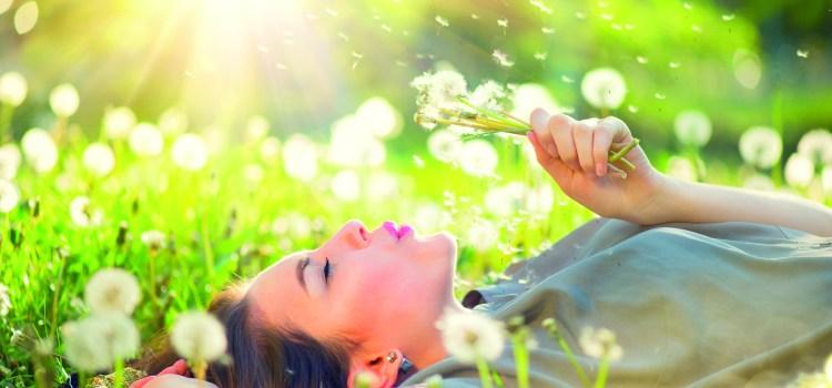 Frau liegt in Wiese und pustet Pusteblume. Pollen fliegen. allergische Beschwerden