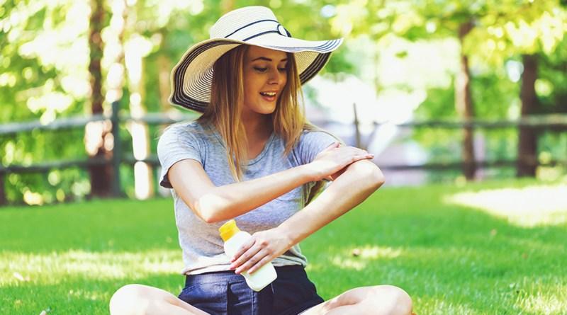 Frau mit Sonnenhut sitzt im Park und cremt sich mit Sonnencreme ein. UV-Belastung