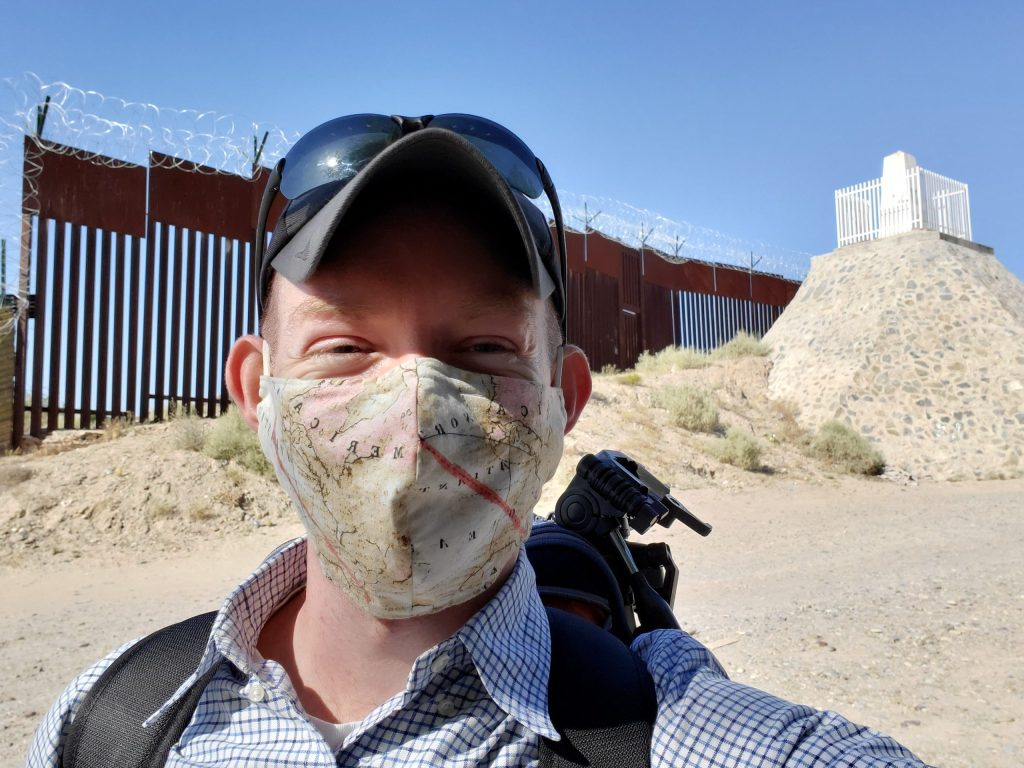 Wearing a mask in front of the US Border Wall