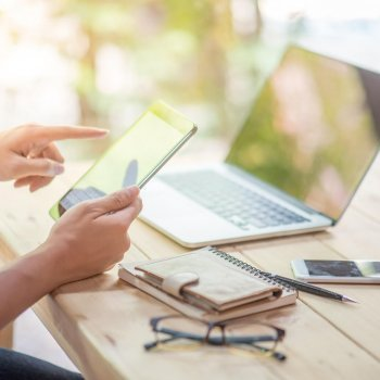 Business man holding tablet and working with laptop and smart phone on wooden office desk in workspace for business information management or search engine optimization concepts
