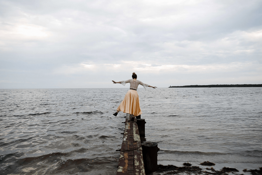 Woman balancing on dock over ocean