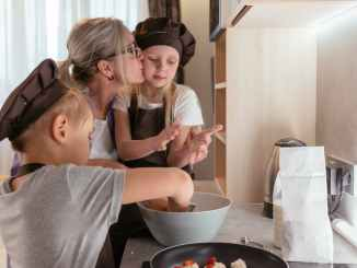 elderly woman kissing granddaughter in her cheek while cooking