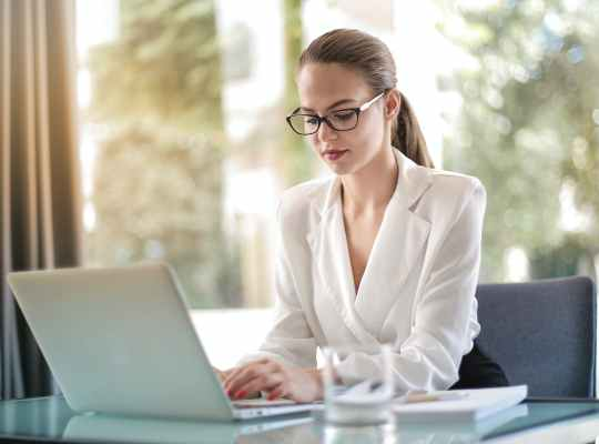 concentrated female entrepreneur typing on laptop in workplace
