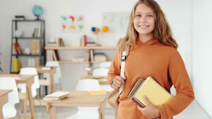 woman in orange long sleeve shirt holding white tablet computer