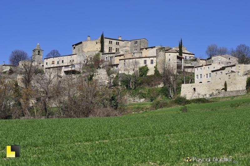 Le village d'Autichamp au soleil sous un ciel bleu, vu d'un champ de blé vert