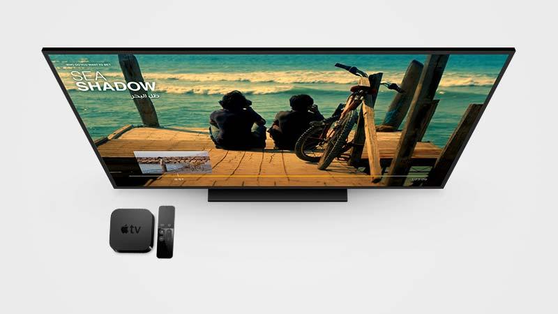 جهاز الاستقبال Apple TV 4 بجانب شاشة كبيرة