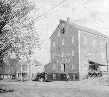 """Flour mill known as the """"Red Mill"""". The Corydon Steam Mill Company was built in 1834, and was powered by steam not a water wheel. It was a frame building of 4 stories and an attic. It was located on the SE corner of Chestnut and Mulberry Streets and was in operation for about 90 years. Eventually L.A. Reasor, who lived next door bought the old mill, tore it down and built a large garage and filling station. This information was taken from a book, """"The Streets of Corydon"""" by the late Fred Griffin."""
