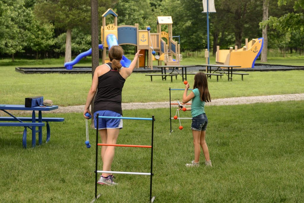 Family playing ladder toss at the park and using math to keep track of the score, helping build numeracy understanding in children. Math games for kids are a lot of fun