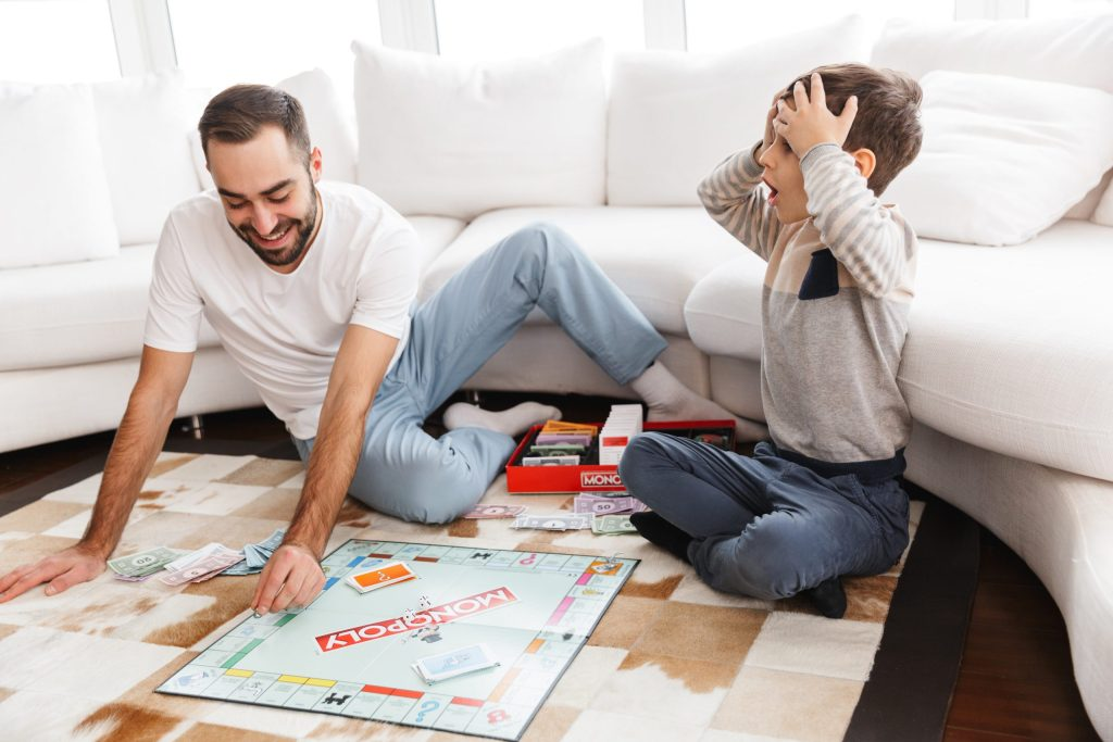 Cheerful young father playing monopoly with his little son while sitting on a floor at the living room and practicing their math skills together