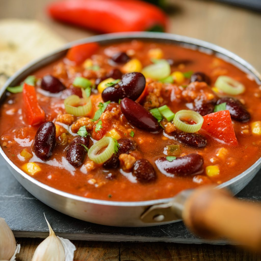 A pan of vegan chili with beans, peppers, tomatoes, and green onions on it.