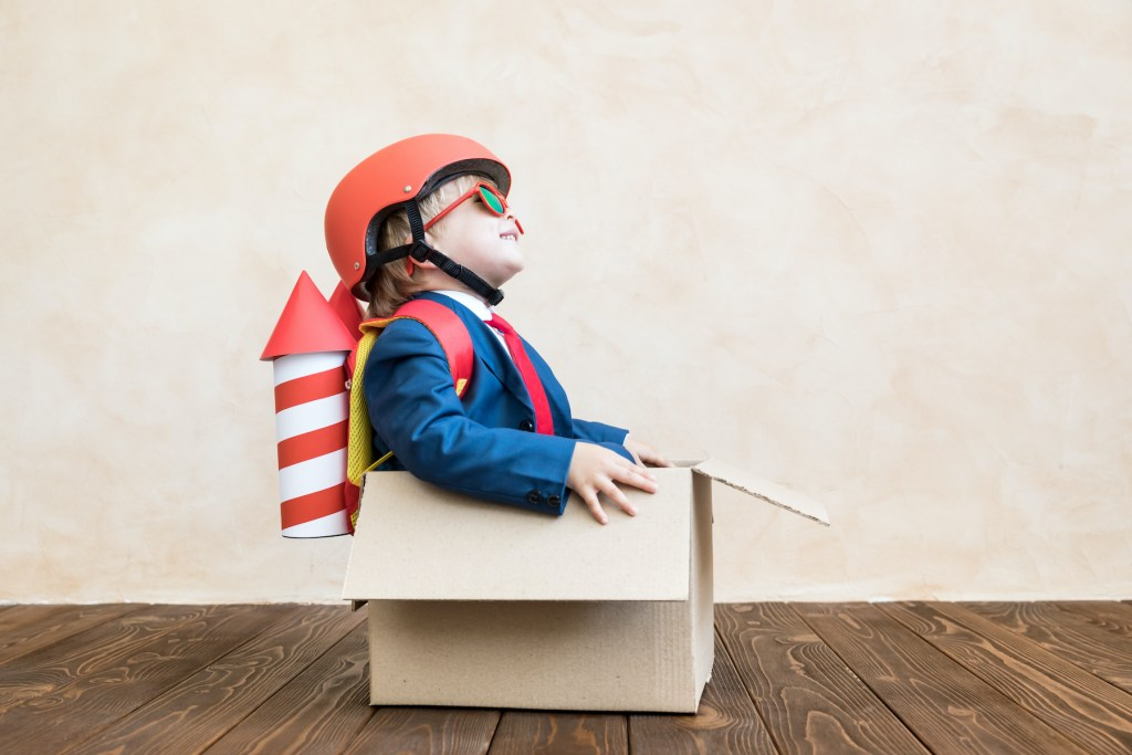 Happy child playing at home. Rocket boy having fun. Success, creative and imagination concept